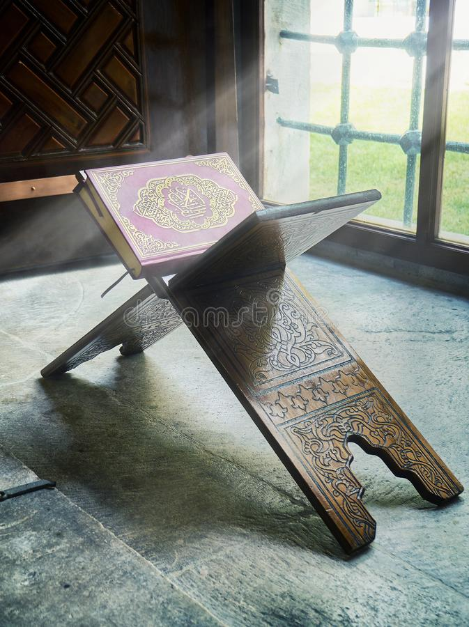 A Quran over a wooden stand enveloped in a ray of divine light. stock photo