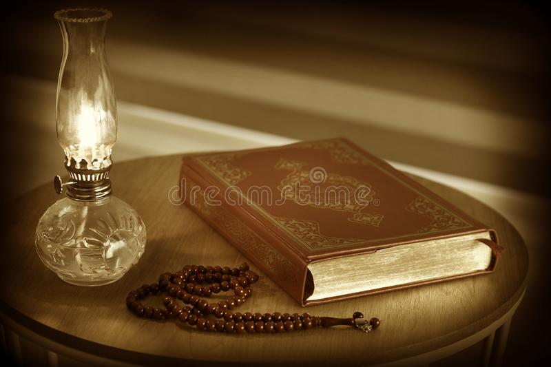 Quran, rosary beads and oil lamp on a wooden stand. stock photography