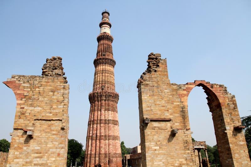 Qutb Minar met voorgrond geruïneerde bogen, Delhi stock afbeelding