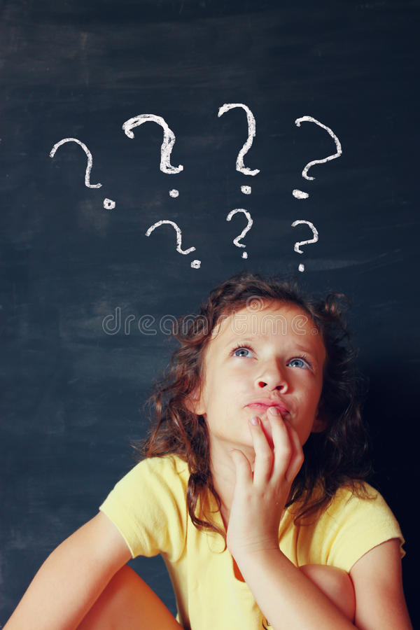 Qute kid next to chalkbord thinking' with many question marks symbols stock photos