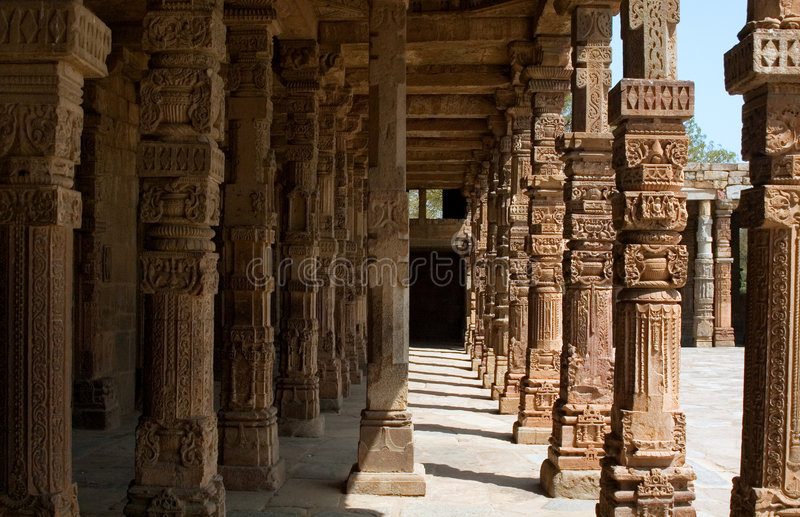 Qutub minar. Consists of a rectangular courtyard enclosed by cloisters, erected with the carved columns and architectural members of 27 Hindu and Jain temples stock photography