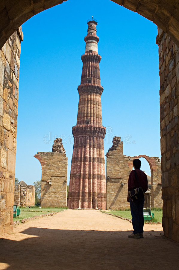 Qutub Minar minaret Delhi. Qutub Minar minaret tower viewed through archway with person in foreground, Delhi, India stock image