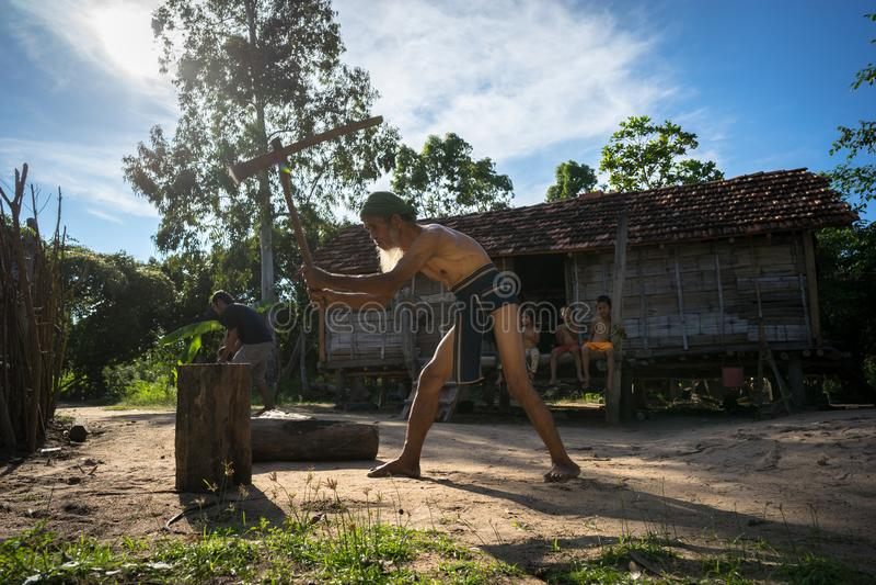 Quy Nhon Wietnam, Oct, - 22, 2016: Silny stary człowiek rozszczepia drewno z cioską w wsi w Quy Nhon obraz stock