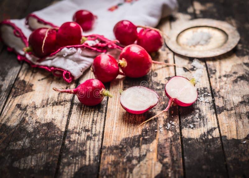 Rábano orgánico fresco con la sal en la tabla de cocina rústica Comida simple imágenes de archivo libres de regalías