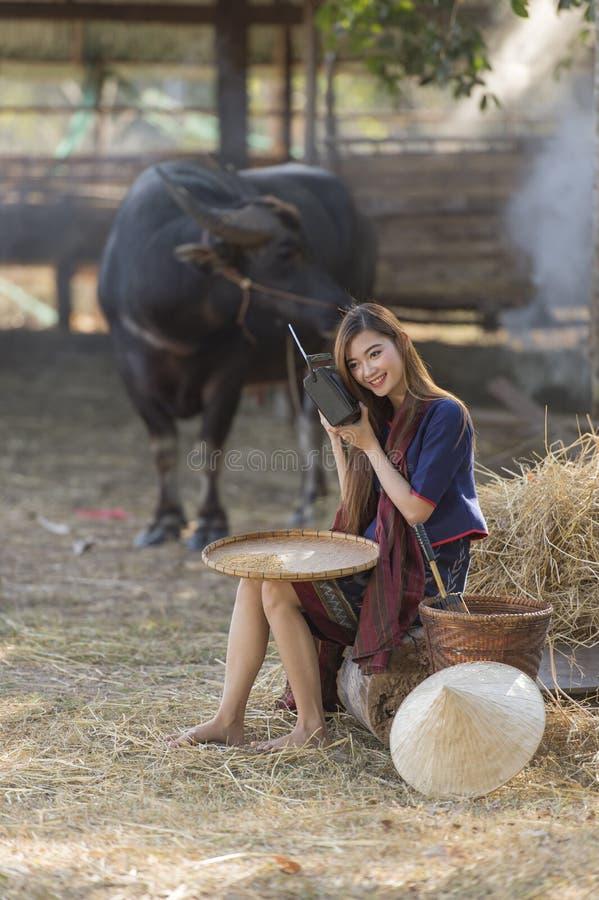 Rádio de escuta em seu fundo da exploração agrícola, campo Tailândia do fazendeiro tailandês da mulher imagens de stock