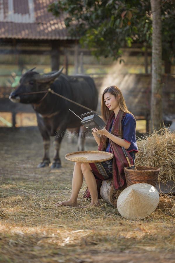 Rádio de escuta em seu fundo da exploração agrícola, campo Tailândia do fazendeiro tailandês da mulher fotos de stock