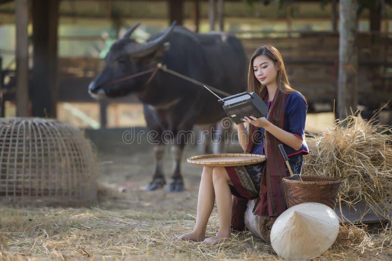 Rádio de escuta em seu fundo da exploração agrícola, campo Tailândia do fazendeiro tailandês da mulher fotografia de stock royalty free