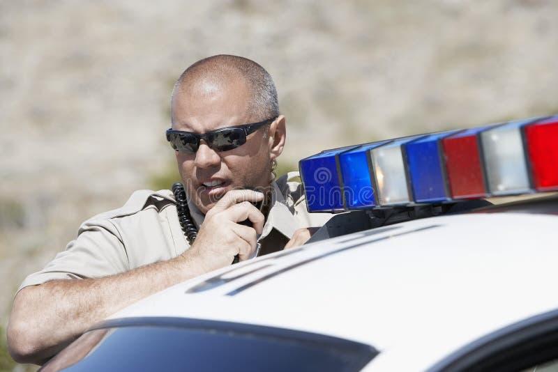 Rádio de Using Two Way do agente da polícia foto de stock
