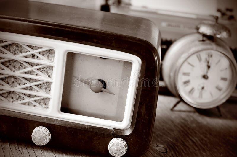Rádio, despertador e máquina de escrever antigos, na tonificação do sepia imagem de stock
