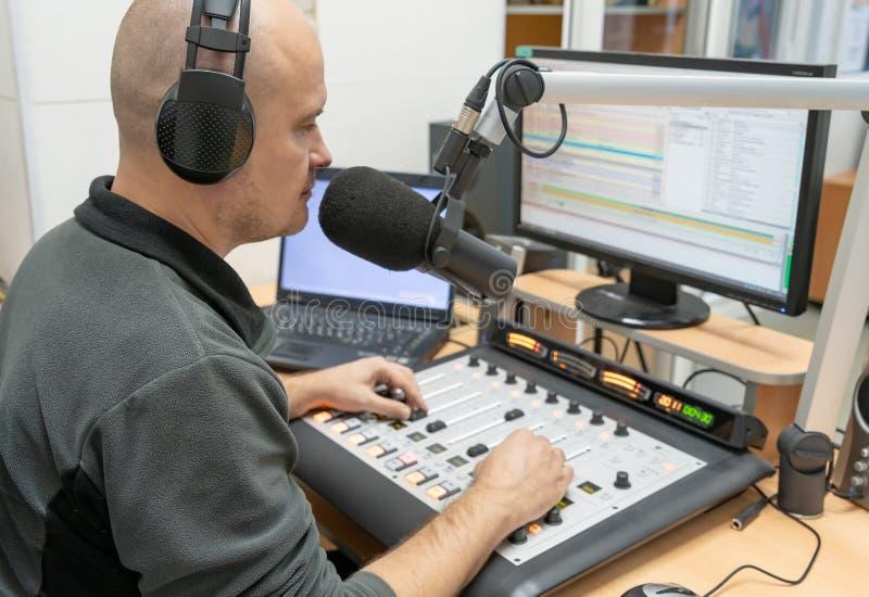 Rádio DJ do homem que senta-se no telecontrole com os fones de ouvido na posição de trabalho imagens de stock