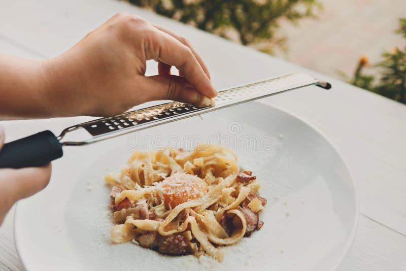 Râpez le parmesan sur le carbonara italien traditionnel de pâtes avec le lard et l'oeuf photo libre de droits