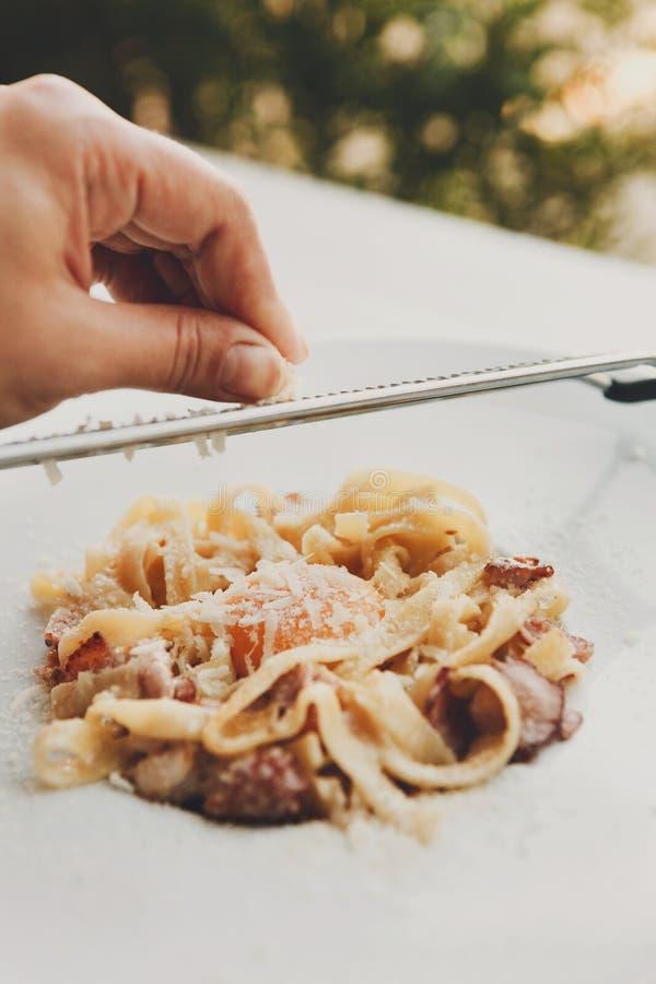 Râpez le parmesan sur le carbonara italien traditionnel de pâtes avec le lard et l'oeuf photographie stock libre de droits