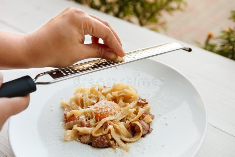 Râpez le parmesan sur le carbonara italien traditionnel de pâtes avec le lard et l'oeuf photographie stock
