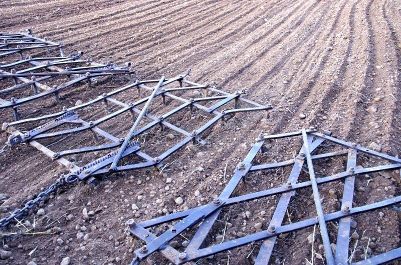 Râteau de herse de machines d'agriculture sur le champ labouré images stock
