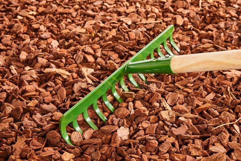 Râteau de jardin au-dessus de paillis de déchet de bois photographie stock libre de droits