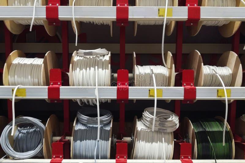 Różni elektryczni biel kable Depeszuje ranę w skeins i pierścionki Elektryczne drutu kabla produktów próbki w sklepie obrazy royalty free