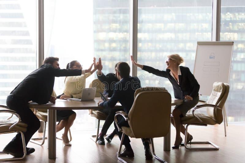 Różnorodna wykonawcza biznes drużyna daje wysokości pięć w nowożytnym biurze obrazy royalty free