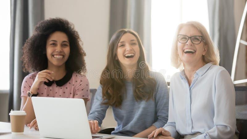 Różnorodni szczęśliwi potomstwa i stary busineswomen śmiać się angażowali w spotkaniu obrazy royalty free
