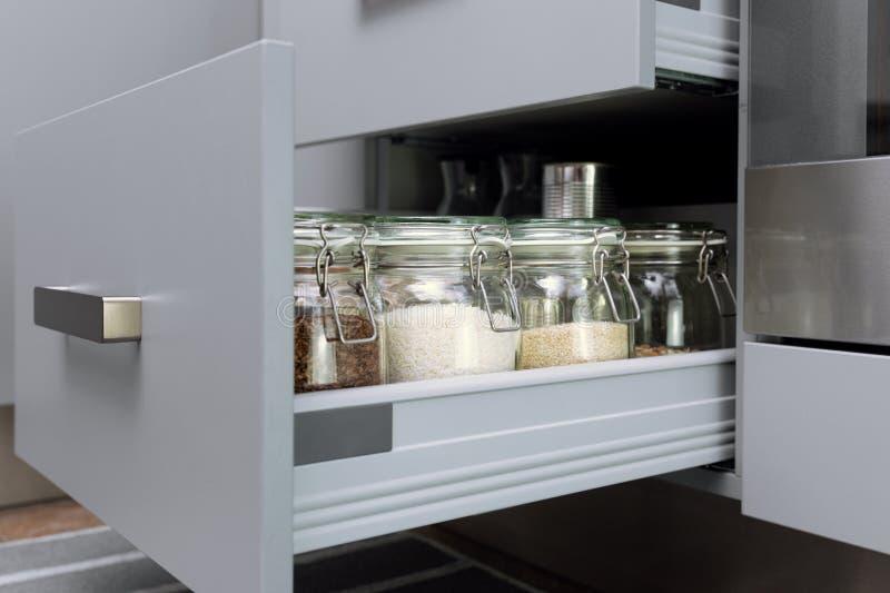 Różnorodni ziarna w składowych słojach w hutch, biała nowożytna kuchnia w tle Mądrze kuchenna organizacja obrazy stock