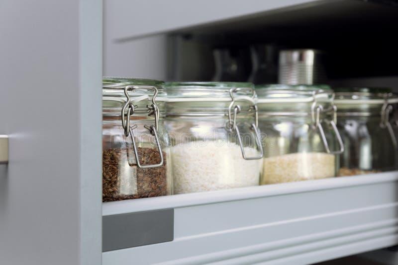 Różnorodni ziarna w składowych słojach w hutch, biała nowożytna kuchnia w tle Mądrze kuchenna organizacja zdjęcia royalty free