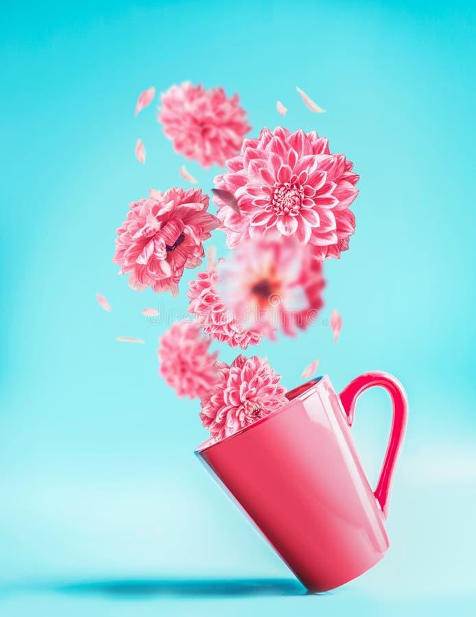 Różowa filiżanka z ładnym lataniem kwitnie przy turkusowego błękita tłem Kreatywnie kwiecisty przygotowania objętych kwiaty Urodz obraz royalty free