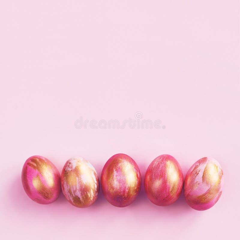 Różowi Easter jajka z pasiastą złotą farbą fotografia royalty free