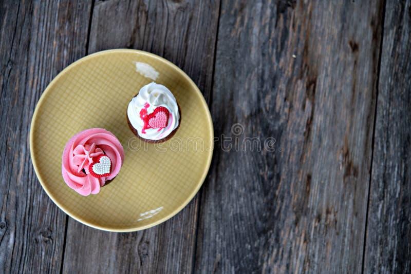 Różowi i biali słodka bułeczka z sercem na drewnianej ziemi obrazy royalty free