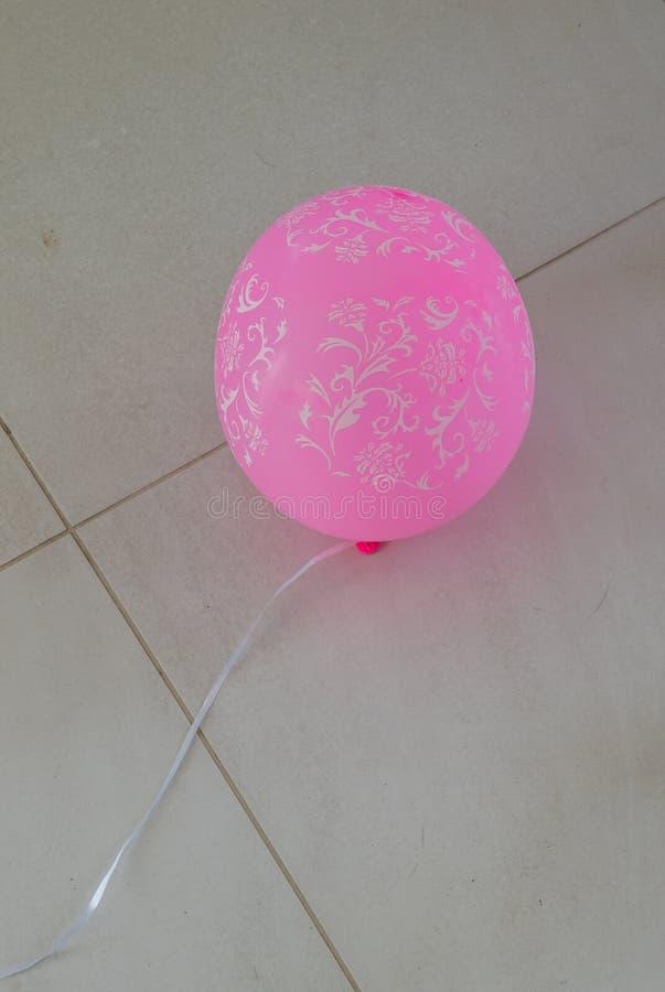 Różowy balon na kafelkowej podłodze obraz royalty free