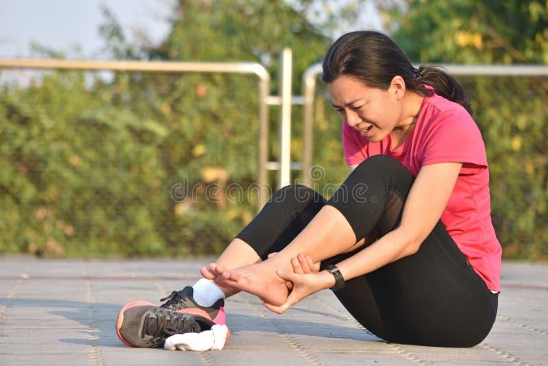 Rührender Fuß des weiblichen Läufers in den Schmerz wegen des verstauchten Knöchels lizenzfreie stockbilder