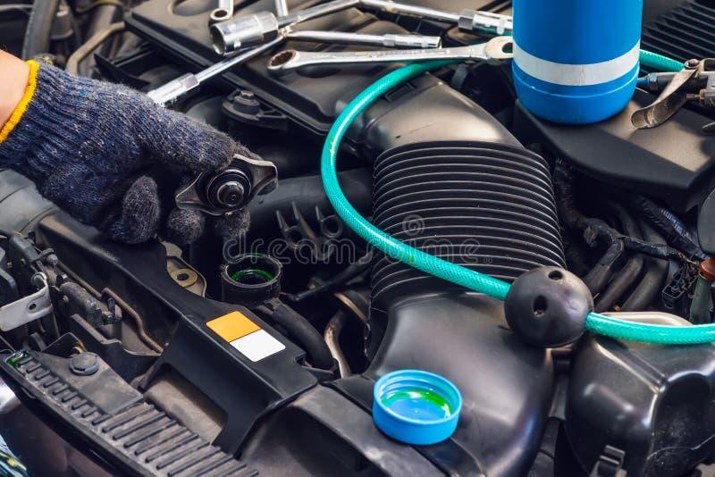 Ręka mechanika czeka woda w samochodowym grzejniku i dodaje wodnego antIfreeze coolant fluid samochodowy grzejnik przy garażem, u zdjęcie royalty free