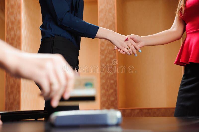 Ręka swiping kartę debetową na pos terminal Ludzie biznesu trzyma konferencję i dyskutuje strategie w biurze zdjęcie stock