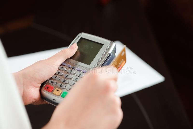 Ręka swiping kartę debetową na pos terminal Ludzie biznesu trzyma konferencję i dyskutuje strategie w biurze fotografia stock
