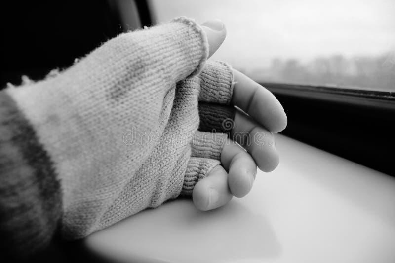 Ręka z starą rękawiczką który brakuje palcowych wierzchołki odpoczywa na stole z widokiem outside w czarny i biały zdjęcie royalty free