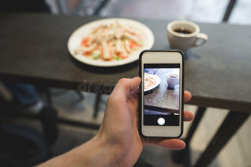 Ręka z telefonem robi fotografii jedzenie w restauracji Sałatkowa i kawowa fotografia na smartphone fotografia stock