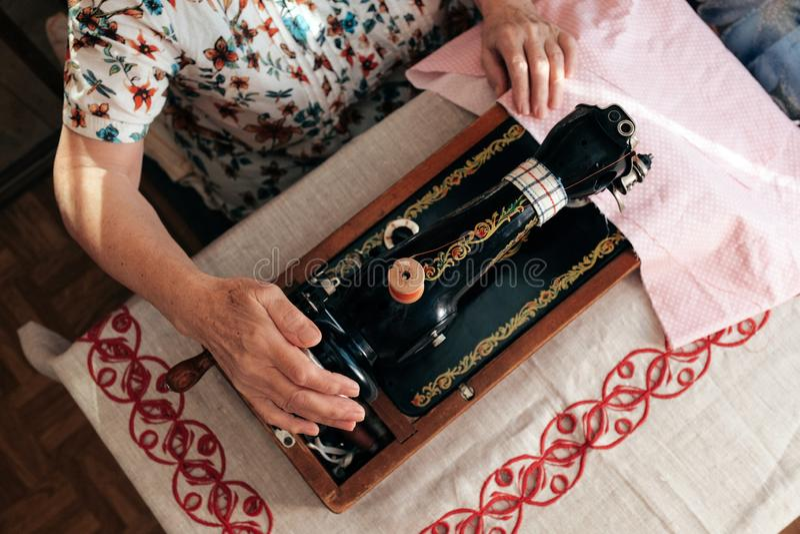 Ręki babcia używają retro ręczną szwalną maszynę zdjęcie stock