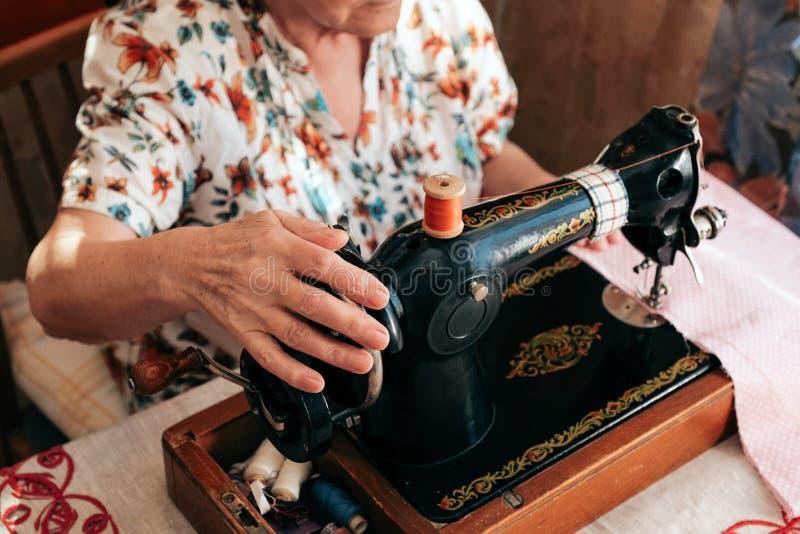 Ręki babcia używają retro ręczną szwalną maszynę zdjęcia stock