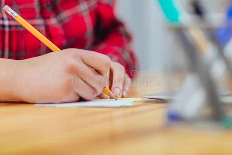 Ręki młoda dziewczyna która pracuje w biurze Podczas ten czasu trzyma ołówek w jego rękach napisał praca planie dla obrazy royalty free