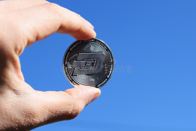 Ręki mienia srebra junakowania moneta na niebieskiego nieba tle obraz stock