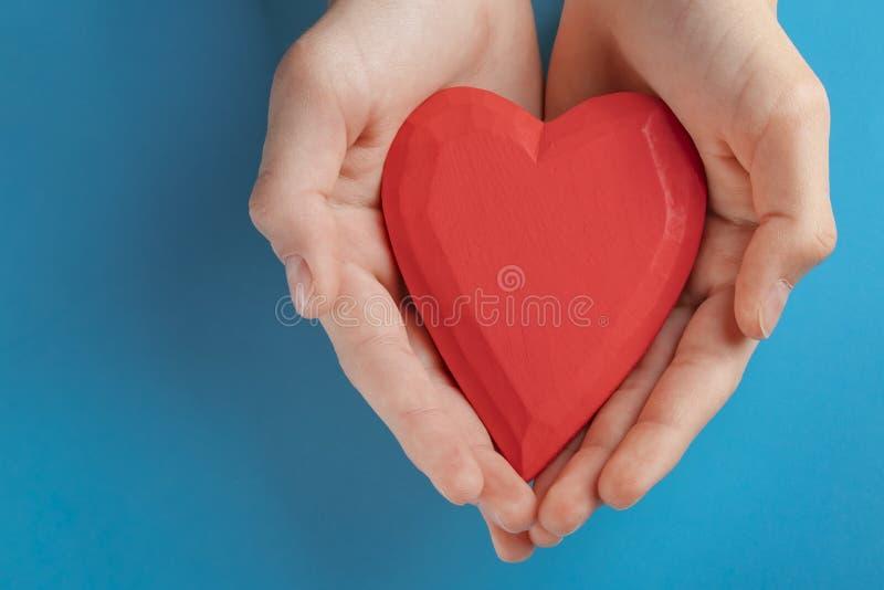 Ręki nastolatka dziecko trzyma czerwonego drewnianego serce w ich rękach niebieska tła obraz royalty free