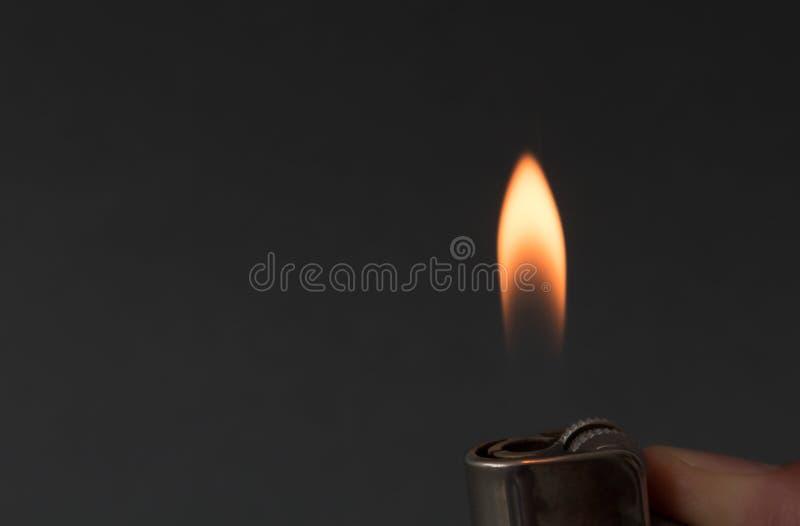 Räcka att antända brand med tändaren på mörk bakgrund royaltyfri foto
