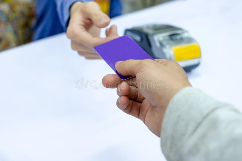 Räcka att betala kreditkorten på betalningterminalen med kassörskan fotografering för bildbyråer