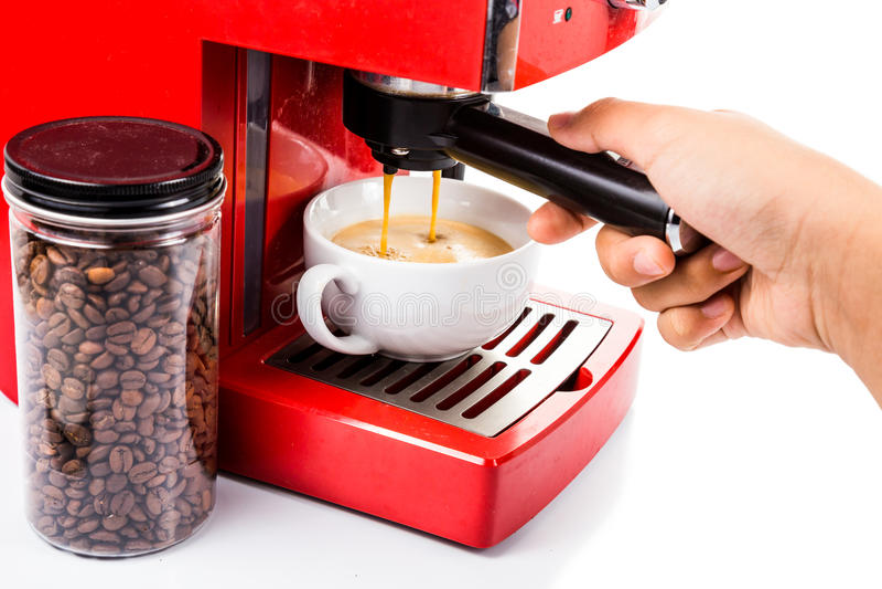 Räcka att brygga kaffe med en ljus för espressokaffe för röd färg maskin arkivfoton