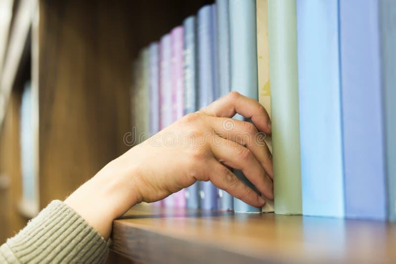 Räcka att dra av en bok - - hyllan royaltyfria bilder