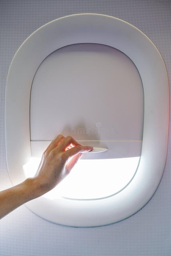 Räcka att dra ner eller up flygplanfönstergardinen, medan resa arkivfoton