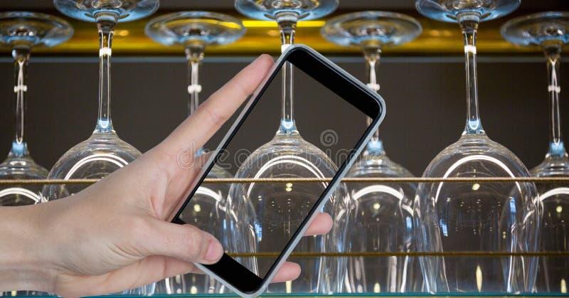 Räcka att fotografera uppochnervända vinexponeringsglas till och med den smarta telefonen arkivbilder