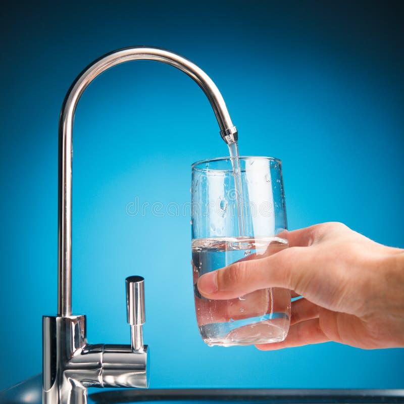 Räcka att hälla ett exponeringsglas av vatten från filterklappet royaltyfri fotografi