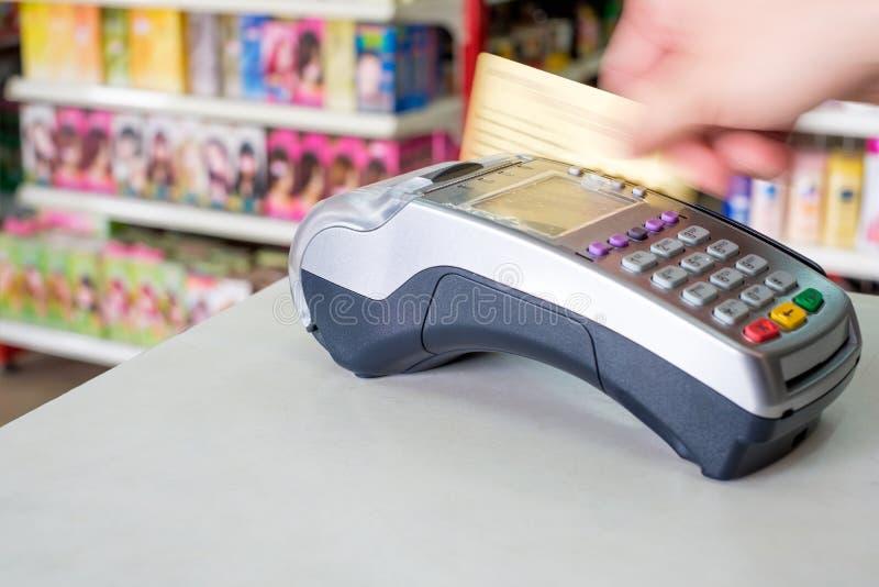 Räcka att nalla kreditkorten på betalningterminalen i lager royaltyfria bilder