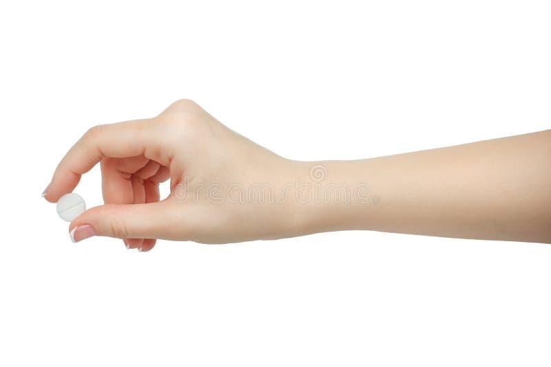 Räcka att rymma en preventivpiller mellan tummen och pekfingret som isoleras på vit bakgrund manicured hand arkivfoto