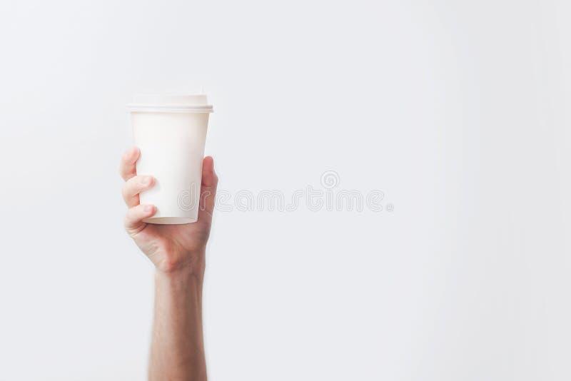 Räcka att rymma en råna med läckert kaffe i ett kafé på vita lodisar royaltyfria bilder