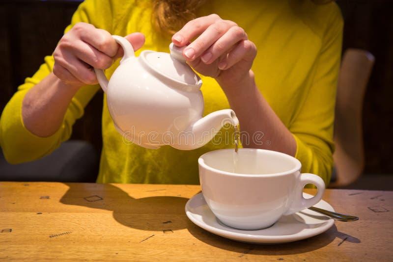 Räcka att rymma ett hällande te för tekanna i en vit kopp arkivbilder